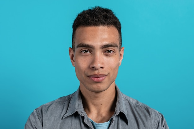 Closeup studio  portrait young cheerful mulatto guy in a dark.