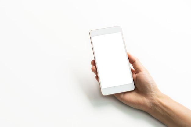 クローズアップスタジオは、スマートフォンの空白の画面を持って手を撮影しました。白い背景で隔離。スペースをコピーします。