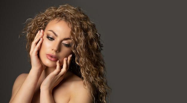 巻き毛の青々とした髪と輝く健康な肌を持つゴージャスなブロンドの女性のクローズアップスタジオショット。テキスト用のスペース