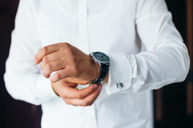 Крупным планом стильные часы на руке жениха, который смотрит на циферблат белая рубашка