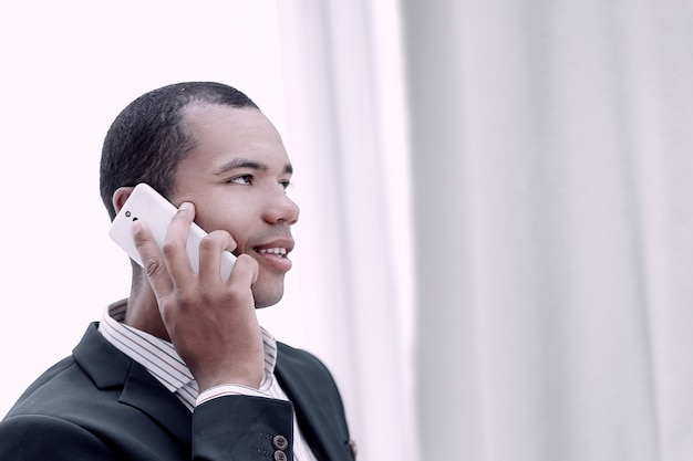 Крупный план. успешный бизнесмен разговаривает по мобильному телефону.