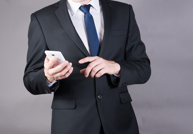 Closeup of a successful businessman using mobile smart phone