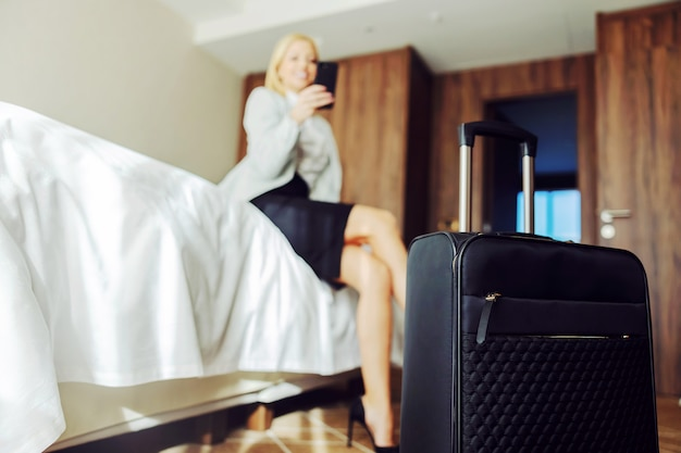 Closeup of suitcase in hotel room. businesswoman sitting on the bed and using a smart phone. she is at the symposium.