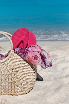 Closeup of summer straw bag with flip flops on the beach