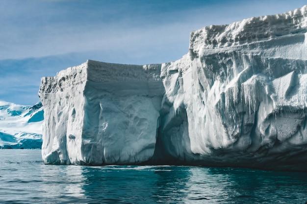 파란색과 흰색 색조의 근접 촬영 햇볕에 쬐인 빙산 남극 장면 놀라운 눈 덮인 얼음 블록