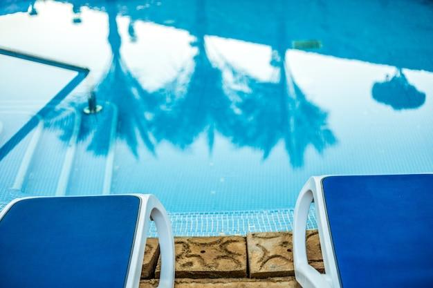 Шезлонги крупным планом и бассейн с отраженными пальмами в воде