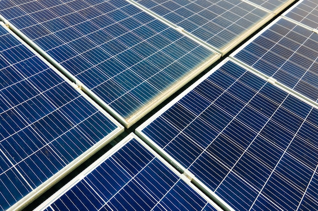 Closeup of surface of blue photovoltaic solar panels mounted on building roof for producing clean ecological electricity. production of renewable energy concept.