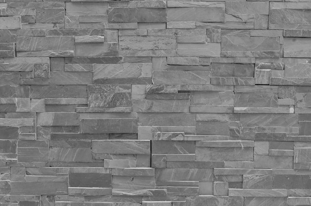 Closeup surface brick pattern at old black stone brick wall textured background in black and white tone