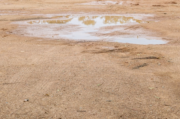 Closeup surface soil ground after rain with tire marks textured background