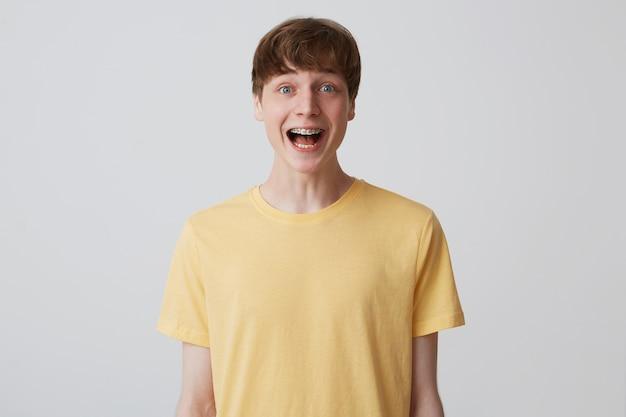 Primo piano del giovane attraente sorpreso con taglio di capelli corto