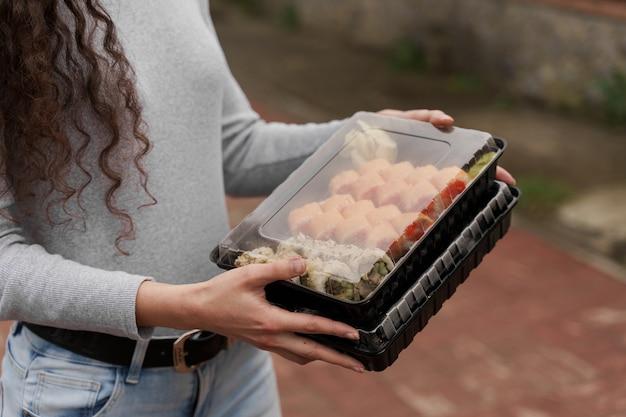 상자 건강 식품 배달 온라인 서비스에 근접 촬영 초밥. 소녀는 손에 2 개의 초밥 세트를 보유하고 있습니다. 일본 요리 롤, 간장, 와사비.