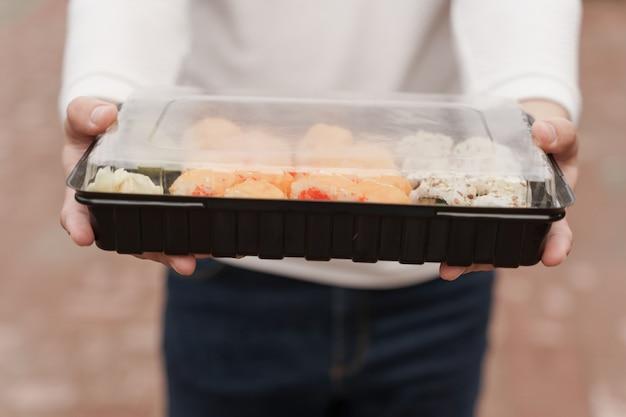 Крупным планом суши в коробке онлайн-сервис доставки здоровой еды. мужчина в белой одежде дарит вам суши-сет. роллы японской кухни, соевый соус, васаби.
