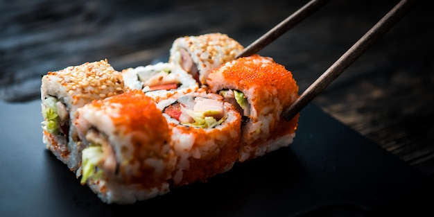 Closeup of sushi rolls with chopsticks