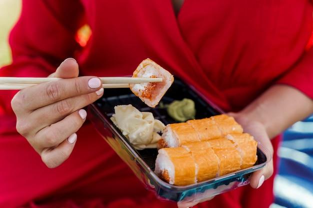 クローズアップ寿司セット。赤いドレスを着た魅力的な女の子が、箸を手に寿司を握っている。宅配便で配達された、かわいい女性のための寿司セット。寿司、わさび、生姜が入った黒い箱。