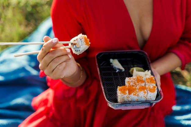 근접 촬영 초밥 음식 배달을 설정합니다. 섹시 한 여자 손에 젓가락으로 초밥을 보유하고있다.