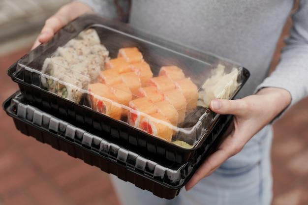 근접 촬영 초밥 상자 건강 식품 배달 온라인 서비스에 설정합니다. 소녀는 손에 2 개의 초밥 세트를 보유하고 있습니다. 일본 요리 롤, 간장, 와사비.