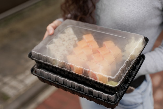 근접 촬영 초밥 상자 건강 식품 배달 온라인 서비스에 설정합니다. 소녀는 손에 2 개의 초밥 세트를 보유하고 있습니다.