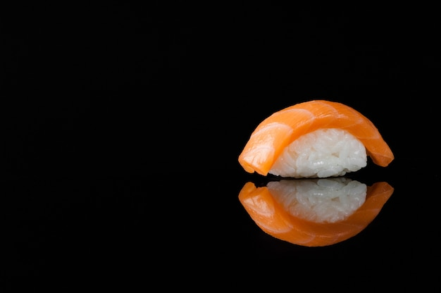 Closeup of sushi with rice on black background with reflection