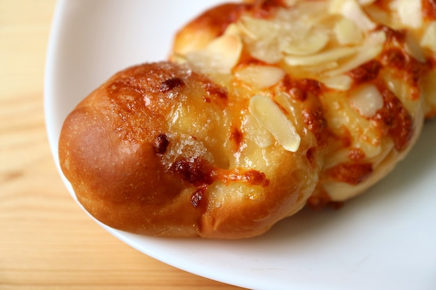 Closeup of sweet almond twist bread on a white plate