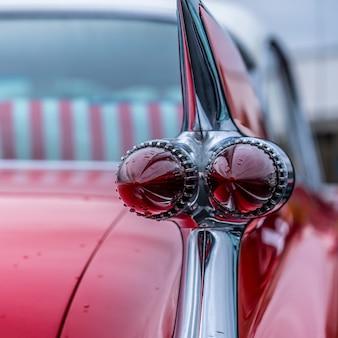 Primo piano del fanale posteriore di un'auto d'epoca rossa parcheggiata all'aperto durante la pioggia