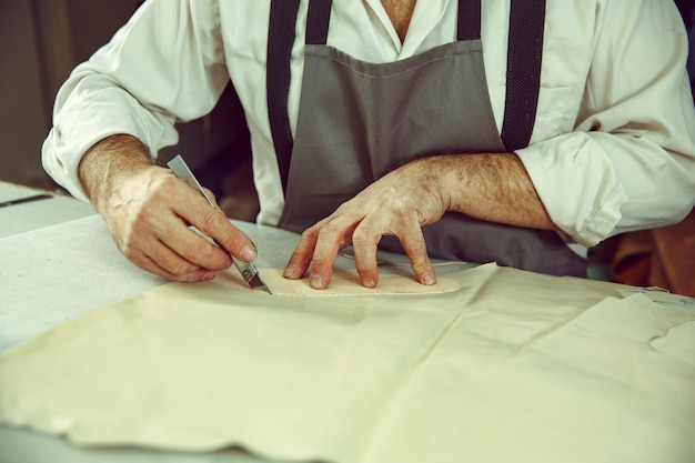 Closeup of tailors table with male hands tracing fabric making pattern for clothes in traditional atelier studio. the man in female profession. gender equality concept
