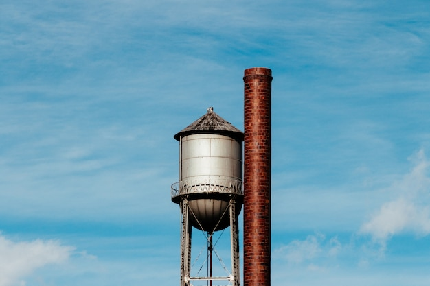 Closeup of a tall water tower with a metal large pipe next to it