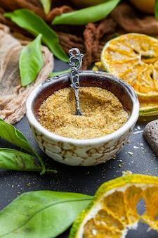 Primo piano della polvere di mandarino in una ciotola su un tavolo circondato da foglie e mandarini secchi