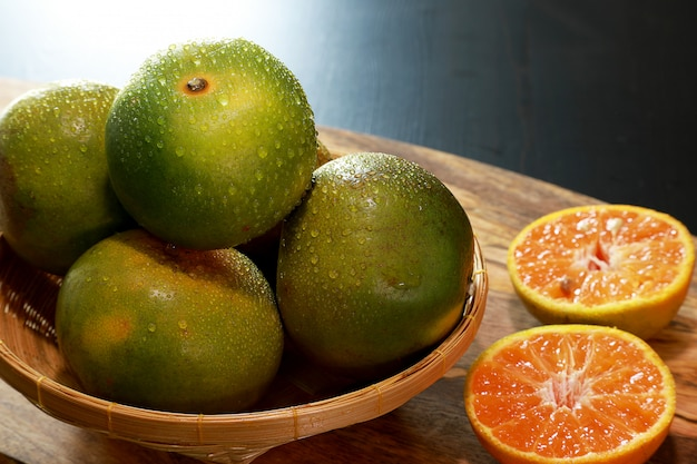Tangerines или клементины или апельсины крупного плана, в деревянной корзине на деревянном столе. концепция фруктов.