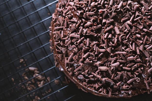 Closeup of tasty chocolate cake with chocolate chunks on baking sheet.