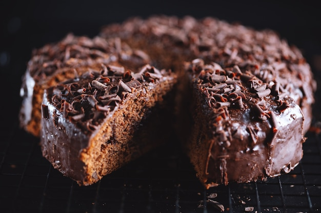Primo piano di gustosa torta al cioccolato con pezzi di cioccolato su teglia.