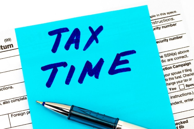Closeup of tax time - written on a sticky notes.