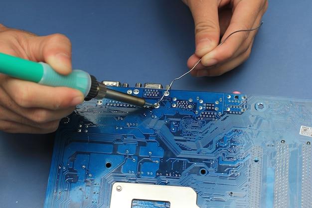 Closeup of a technician's hands soldering a computer mainboard