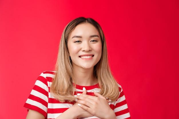Primo piano tenero toccato giovane affascinante ragazza bionda asiatica premere palmi cuore grato sorridente ampiamente ap...