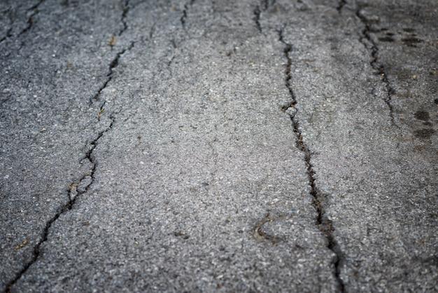 Крупным планом текстурированный фон трещин на асфальте сельской дороге