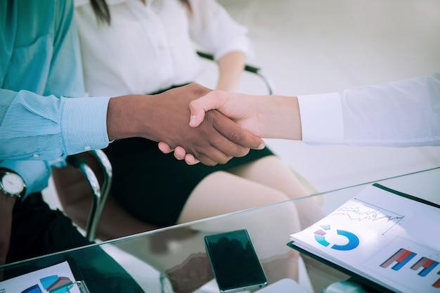 Крупным планом. финансовые партнеры, пожимая руки за стол. концепция выгодного партнерства