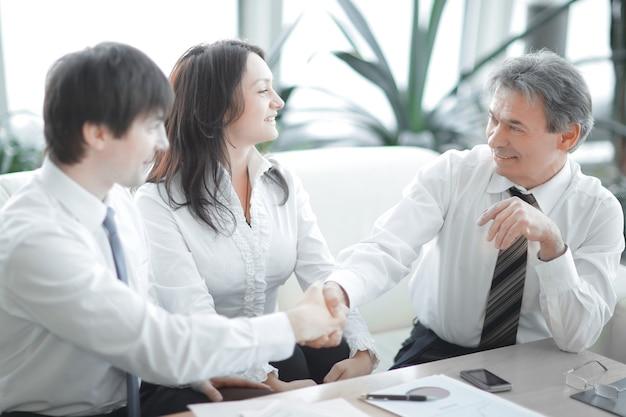 Крупным планом. финансовые партнеры, пожимая руки над столом в офисе