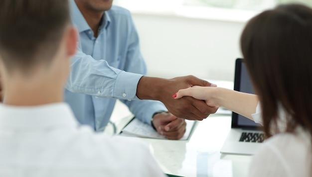 Крупным планом рукопожатие сотрудников на рабочем месте концепция сотрудничества