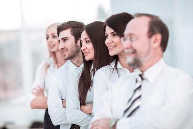 근접 촬영 - 사무실 배경에 다른 사람 뒤에 서 있는 리더와 비즈니스 팀