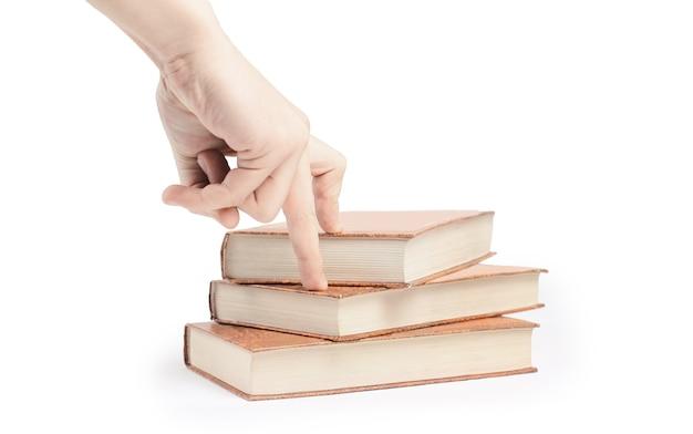 クローズアップ。人はスタックから1冊の本を選んでいます。