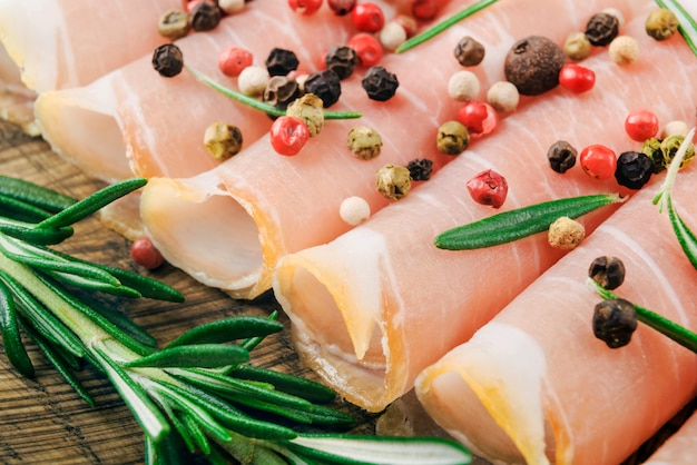 Closeup of thin slices of prosciutto with rosemary and paprika on wooden cutting board