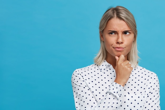 Il primo piano della giovane donna bionda seria premurosa indossa la camicia a pois sembra pensieroso e pensa isolato sopra la parete blu che guarda al lato e che tocca il suo mento
