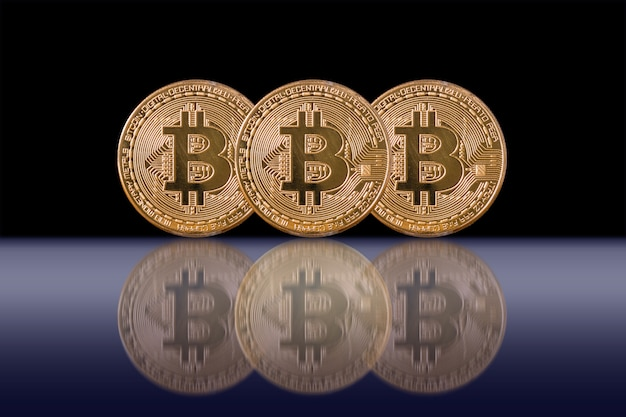 Closeup three bitcoins mockup with reflection on black color background, cryptocurrency and isolate