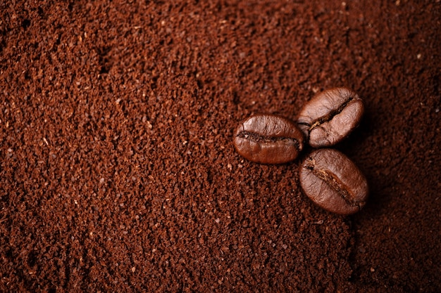 Closeup of three coffee beans at the mixed heap of roasted coffee