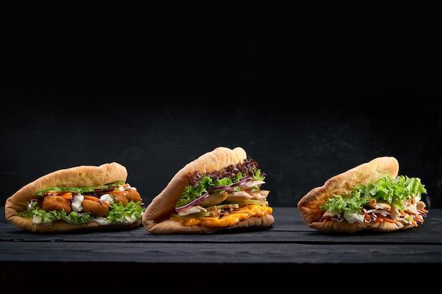 나무 배경에 근접 촬영 세 가지 맛 샌드위치 또는 햄버거