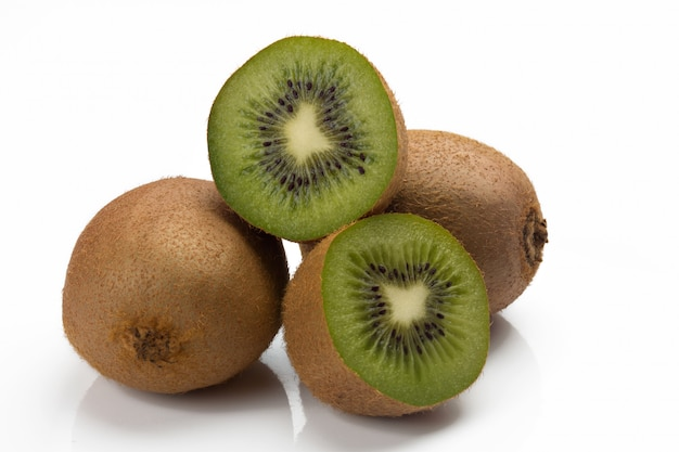 Closeup of three kiwis, two whole and one cut.