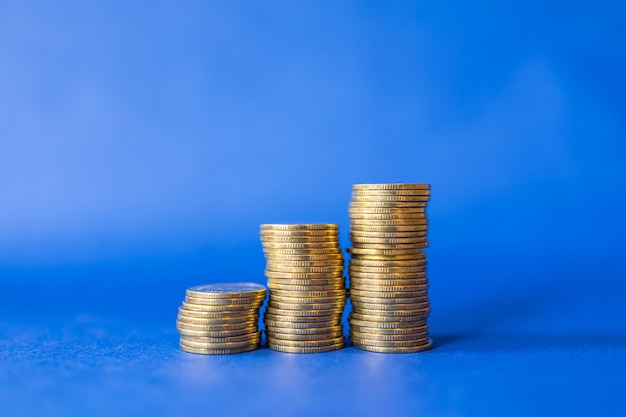 Closeup of three stack of gold coins on blue background