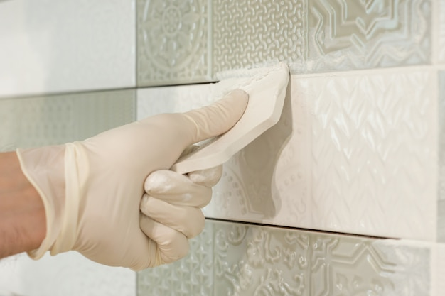 Closeup of tiler hand rubbing tile