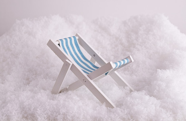 Closeup of a tiny toy sunbed in the snow