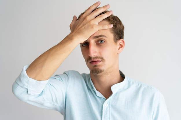 Closeup of tired disappointed blonde guy with face palm gesture.