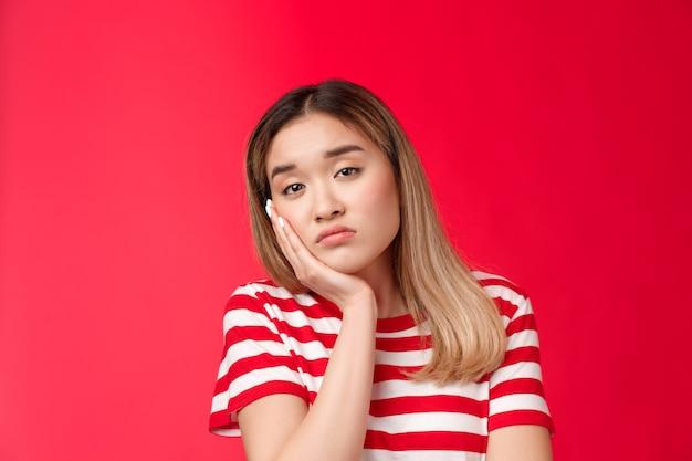 クローズアップ疲れた女の子は無関心退屈をため息をつきたくない表情カメラ痩せた顔手のひらがアスリーに落ちる...